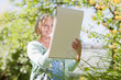 Smiling woman drawing on sketch pad outdoors