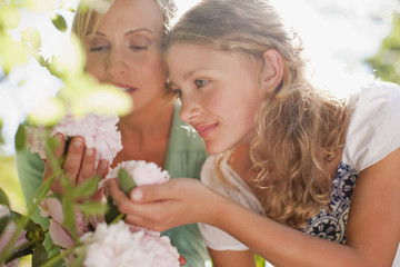 Mother and daughter smelling flowers
