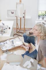 Woman sitting on floor of art studio