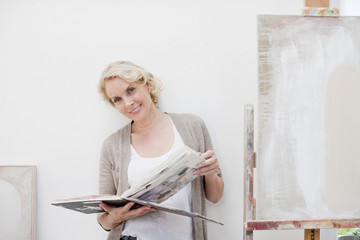 Smiling woman looking through book next to canvas in art studio