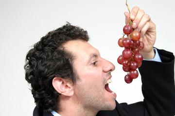Healthy man eating black grapes, healthy food photo