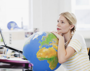 Pensive businesswoman leaning on globe at desk in office