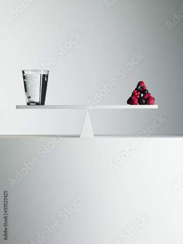 Water and berries balanced on opposite ends of seesaw