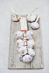 Purple garlic bunch on wooden board
