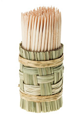 Bunch of wooden toothpick in round wattled straw holder