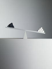 Sugar cubes tipping seesaw with blueberries on opposite end
