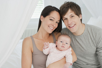 Smiling parents holding baby