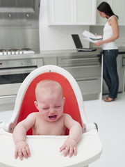 Baby in high chair crying with mother paying bills online in kitchen