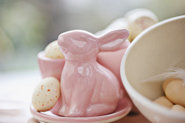 Close up of porcelain Easter bunny and candy eggs
