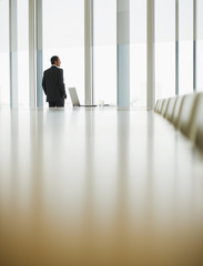 Businessman standing at window of empty conference room