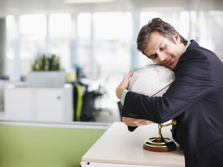 Smiling businessman hugging globe in office