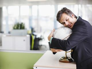 Smiling businessman hugging globe in office