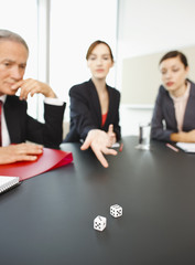 Business people throwing dice on conference room table