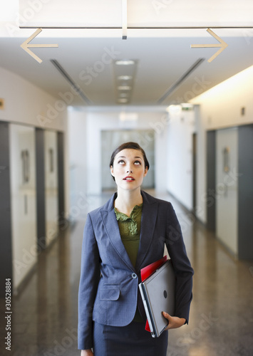 Businesswoman in corridor looking up at arrows pointing opposite directions