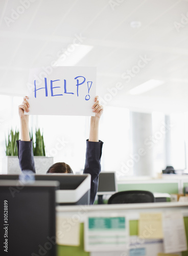 Businesswoman holding ?Help? sign overhead in office