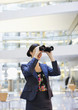 Smiling businesswoman looking through binoculars in office