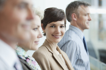 Smiling businesswoman in row of business people