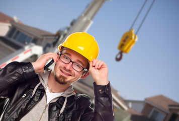 Young Cunstruction Worker on Cell Phone In Front of Crane