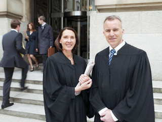 Smiling judges in robes standing outside courthouse