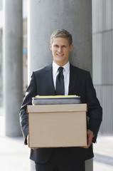 Smiling lawyer holding files and box