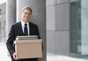 Smiling lawyer holding files and box outside office building