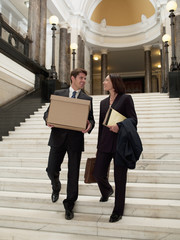 Lawyers carrying files and box down stairs