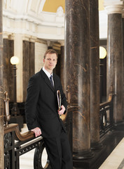 Confident lawyer leaning against railing in corridor