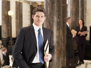 Smiling businessman leaning against pillar in corridor