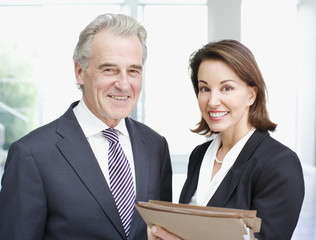Smiling business people holding files in office