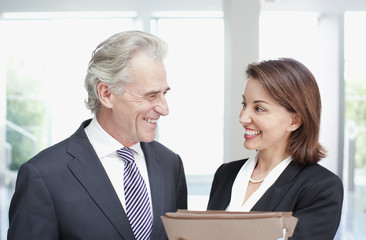 Smiling business people with files