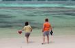 deux enfants sur plage de sable blanc