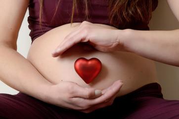 Donna in gravidanza con cuore rosso