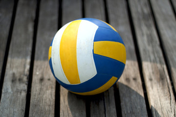 Volleyball ball on wooden to a floor close up