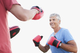 Smiling man boxing with sparing partner
