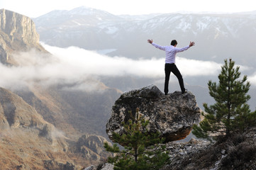 Man on top of mountain with open arms. Conceptual design
