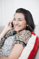 Smiling teenage girl talking on cell phone