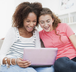 Smiling teenage girls using laptop together