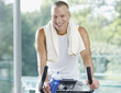 Smiling man sitting on stationary bicycle