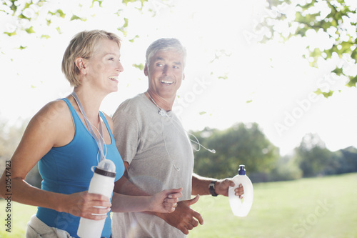 Couple jogging together with water bottles