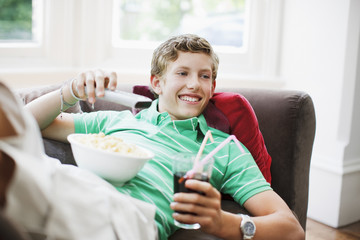 Teenage boy with snacks holding remote control