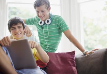Smiling teenage boys using digital tablet together