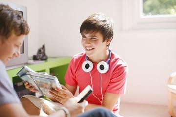 Smiling teenage boys looking at video games