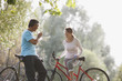 Couple with bicycles drinking water