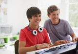 Teenage boy watching friend play electronic piano keyboard