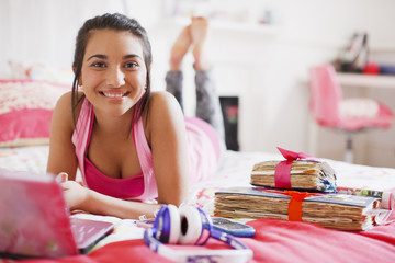 Teenage girl laying on bed using laptop