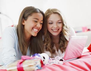 Smiling teenage girls using laptop together