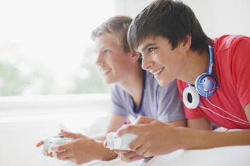 Smiling teenage boys playing video game