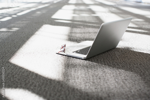 Laptop and eyeglasses on office floor