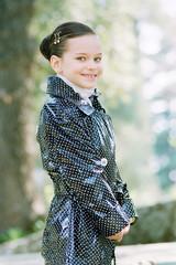 Девочка одетая в плащ в горошек кокетливо улыбается.