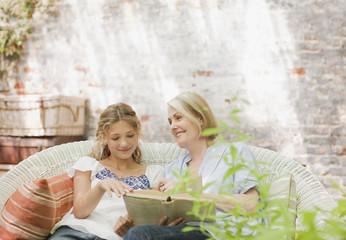 Grandmother and granddaughter enjoying book on patio